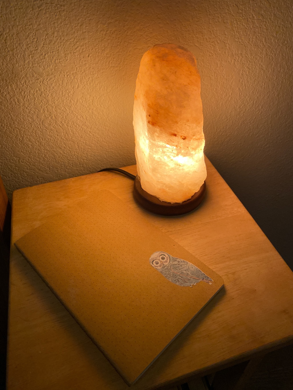 a glowing salt lamp sits on a side table next to a notebook in dim light
